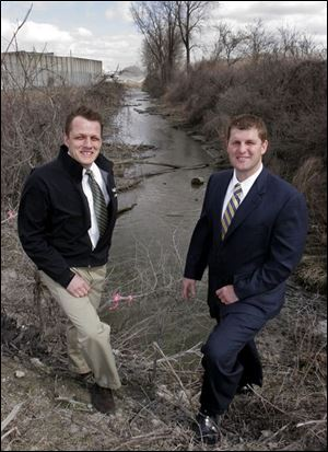 Toledo Councilman Frank Szollosi, left, and his brother, Oregon Councilman Matt Szollosi, discuss Duck Creek, whose rechanneling was the focus of a boundary dispute.
