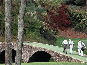 Jack Nicklaus, left, and Gary Player, center, walk across the 