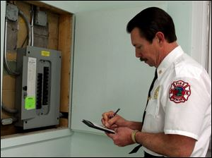 Ron Whipple inspects an electrical box in a Samaria building.