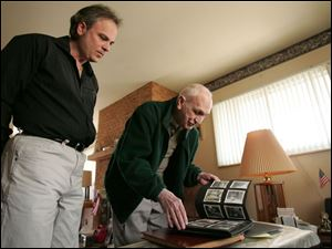 John Smith and his father, Paul, look over old photos in their home, built on the site of one lost in the tornado.