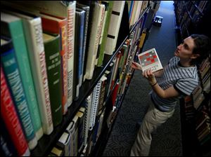 Tricia Gallant shelves books at the main Toledo-Lucas County Public Library, which uses a collection agency.