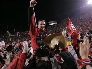 Urban Meyer is carried off the field after his Utah team blasted Brigham Young 52-21 last November. Utah finished 12-0.