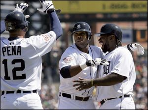 Marcus Thames, center, is greeted by Carlos Pena, left, and Dmitri Young, right, after his grand slam in the third inning.