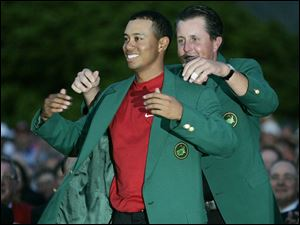 Last year's champion, Phil Mickelson, puts the fourth green jacket on Tiger Woods. Mickelson shot 74 yesterday.