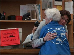Thackeray s assistant manager Lee Post hugs longtime customer Cecilia Arras of Findlay on the bookstore s last day.