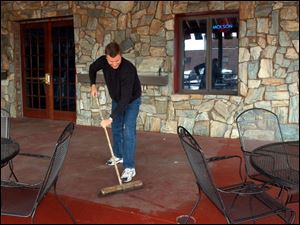 Owner Alva Caple gets the patio ready at the Durty Bird, which he said derives about two-thirds of its business from Hens fans.