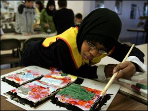 Aisha Deme, 8, of Bowling Green paints tiles that will become part of a larger mosaic for the Islamic School of Greater Toledo.