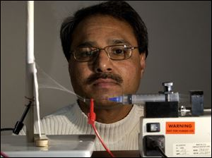 Abdul-Majeed Azad, of UT, checks the progress as a polymer ceramic mixture in a syringe becomes a nanofiber.