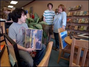Bowling Green High School students Matt Mauk, left, and John Winkle chat with their teacher, Kim Sockman, about the art that will hang in the Grounds for Thought coffee shop.