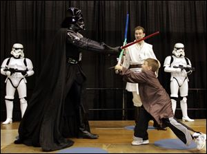Anthony Campbell, 7, of New Albany, Ind., duels with Darth Vader as Simon Needham of London, as a Jedi master, observes.