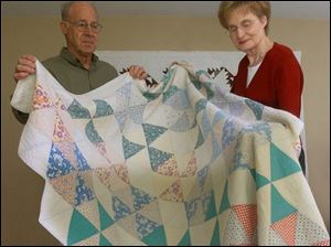 Howard and Carolyn Snyder hold up one of the 18 quilts in their Pettisville home.