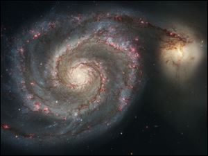 The new Whirlpool Galaxy image showcases the spiral galaxy's classic features, from its curving arms, where newborn stars reside, to its yellowish central core that serves as home for older stars.  The soaring tower is 9.5 light-years or about 90 trillion kilometers high, about twice the distance from our Sun to the next nearest star. A torrent of ultraviolet light from a band of massive, hot, young stars [near the top] is eroding the pillar. The dominant colors in the image were produced by gas energized by the star cluster's powerful ultraviolet light. The blue color at the top is from glowing oxygen. The red color in the lower region is from glowing hydrogen.
