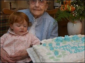 Ella Snyder, 1, has her eyes on the cake of her great-great grandmother, Ester Evenson, at her 100th birthday party.