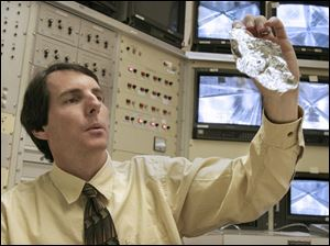 Mr. Murphy examines a section of the solar sail. ATK is one of two solar sail companies competing to win NASA's favor.