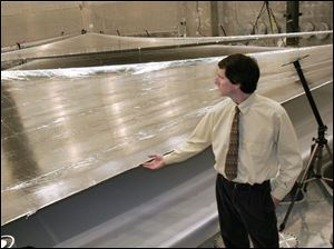 Dave Murphy, principal investigator for ATK Space Systems, ripples the surface of a solar sail panel at the NASA Glenn Research Center's Plum Brook Station in Sandusky.