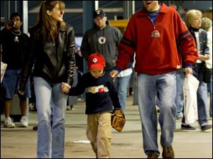 FEA first16p     Andrew Surgo, center, walks with his parents Lisa and Todd during the Mud Hens game Saturday evening 4/16/05.  The Blade/Madalyn Ruggiero