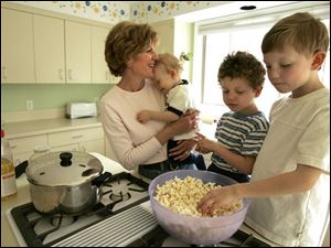 Sue Gilgen of Findlay makes popcorn the old-fashioned way - on the stove - for her children, Patrick, 1, Andrew, 4, and Tommy, 5.