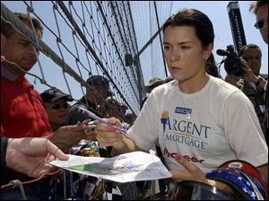 Danica Patrick signs autographs for fans at Indianapolis Motor Speedway. She started racing Go Karts at age 10.