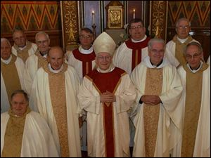 Toledo Catholic Diocese priests with 40 years or more in the priesthood include, from left, the Rev. Robert Weithman, the Rev. Roger Bonifas, the Rev. Joseph O Brien (seated), the Rev. Richard Dunn, the Rev. Benedict Ringholz, the Rev. Michael Ricker, the Rev. Stephen Stanbery, Bishop Leonard Blair, the Rev. Dennis Hartigan, the Rev. Paul Kwiatkowski, the Rev. Nick Weibl, the Rev. Thomas Leyland, the Rev. Frederick Duschl, and the Rev. Martin Donnelly.