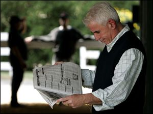 Trainer Nick Zito reads the horse racing news as he awaits the arrival at Pimlico of High Fly, Noble Causeway and Sun King.