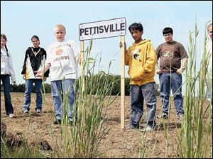 From left, Bethany Iott, Krysta Spiess, Torin Blosser, Jacob Valdez, Victor Garcia, and Stephanie Hamilton hold up their town's sign at the site where MapQuest and the government indicate the town is located. It is not the right location.