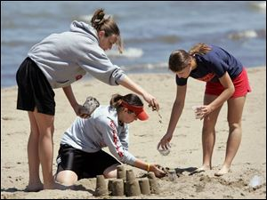 ROV sandcastle 02 - L-R, Mattie Smith, Danie Smith, Emily Bodart, all seniors at Hopewell-Loudon HS in Bascom, OH take a day off at the beach together before Friday's graduation and they all part ways of college. The Blade/Allan Detrich