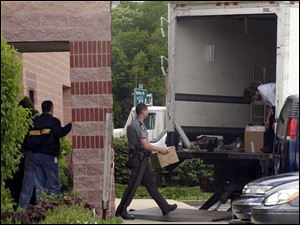 Investigators and Ohio Highway Patrol officers load a truck with materials confiscated from rare-coin dealer Tom Noe's shop in Monclova Township Thursday.
