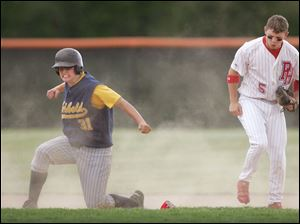 Archbold's Brooks Wagler celebrates after sliding safely into second base under the tag by Patrick Henry's Ben Botjer.