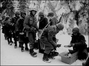 Pfc. John Chavez is fourth in line for a meal. He believes the photo was taken during the Vosges Mountains compaign, probably near Lichtenberg, France.