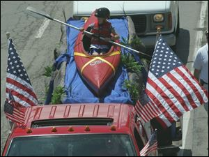 Zack Kurtz rides a kayak on the Calvary Assembly of God bible school float in the Memorial Day parade in downtown Toledo.
