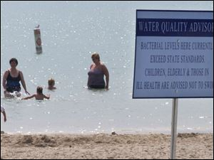 In summers past, some bathers ignore water-quality advisory signs like the one posted at Maumee Bay State Park.