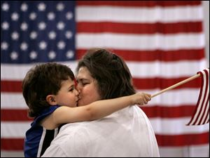 CTY flagday14p 03 - Cyndi Caron gets a big kiss fron her son Tristin, 3, at they listen to the Toledo Interfaith Mass Chior at the rally for the troops at the Lucas County Rec Center, as they bring the crowd to their feet with patriotic songs. The Blade/Allan Detrich