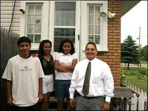 Maria Espinoza, second from left, gathers with Antonio, 14, Eva, 12, and agent Frank Smith at her home in Northwood.