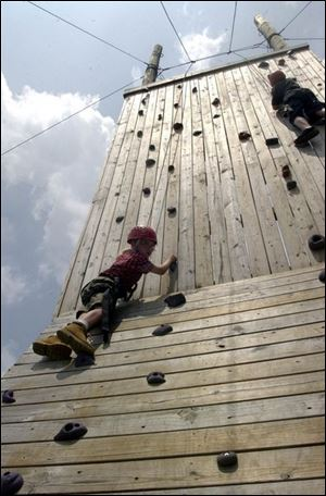 Eric Karr, 12, of Fremont, and Adam Rice, 12, of Monroe, Mich., scale the climbing wall at Camp Libbey in Defiance, Ohio.