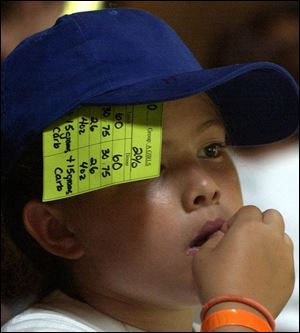 Julianna Hergenreder, 11, of Rossford, uses her hat to hold a card on which she records carbohydrates.