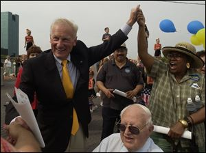 Carty Finkbeiner joins hands with supporter Lola Williams behind former Toledo Mayor Harry Kessler at The Docks after Mr. Finkbeiner announced his plans to run for mayor again.