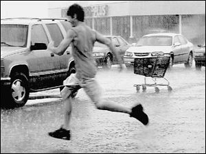A shopper makes a mad dash for his car in a parking lot at Lewis Avenue and Alexis Road
