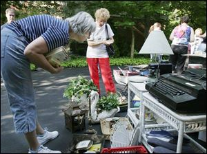 Jan Alexander of Pemberville, left, takes a close look at garage sale items in Perrysburg s Carrington Woods subdivision.