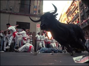 A bull makes a turn around a corner as runners scramble to get out of the way during Pamplona's Running of the Bulls.