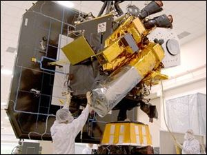 Workers prepare the Deep Impact flyby spacecraft and its impactor (bottom front) for its flight toward Comet Tempel 1.