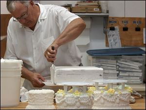 Dennis Wixey spreads the first of two coatings of frosting on the base of the cake. The three tiers in the foreground are completed.