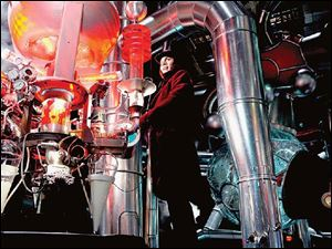 Johnny Depp plays the eccentric candymaker Willy Wonka in his factory wearing a top hat, velvet coat, and a large smile.
