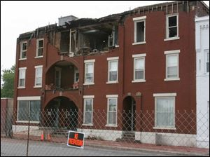 The fire-damaged Clermont Manor Apartments will not be razed at least until next week because of a festival in town.