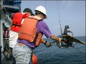 Andy Yehiela, left, and Nathan Hawley launch a Plankton Survey System from the Laurentian