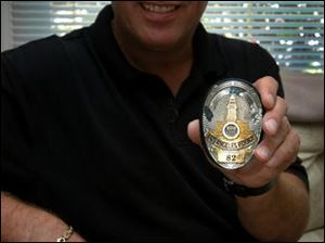 Toledoan Frank T. Balazs holds a police badge he wore in the movie The Island, which opens Friday.