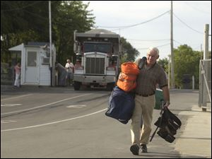 Bob Gase carries gear to the ferry.