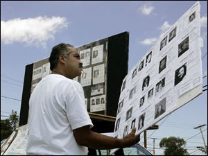 Felix DeJesus of Cleveland looks at photographs of missing children during a rally on Byrne Road. His teenage daughter, Georgina, vanished as she was walking home from school.