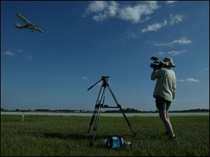 Jendra Jarnagin films an airplane flown by Shane Williams of Phoenix, as he tries to show how Christopher Malhoit's plane swept low to the ground before crashing on May 3, 1996, at the Fulton County Airport in Wauseon.