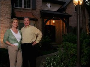 Katie and Steve Branam outside their Sylvania home, which is landscaped with lighting