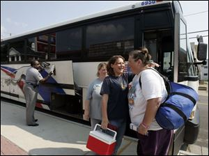 Anna Clark and Ashley Bateson, say good-bye to JoyAnn Powell, who is taking the nationwide bus service to Asheville, N.C.